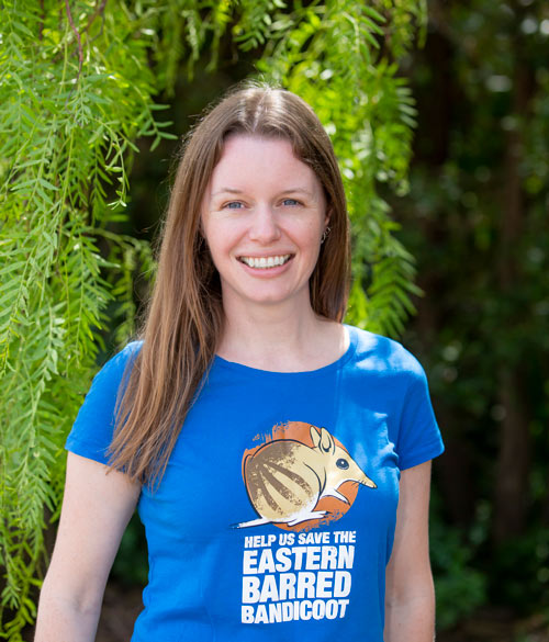 """Amy smiles and wears a tshirt that says """"Help Us Save The Eastern Barred Bandicoot""""."""