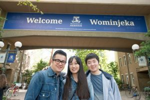 three students standing under a building. The building has a sign that says 'Welcome Wominjeka'