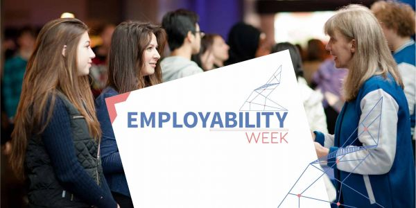 staff and students talking with sign saying employability week