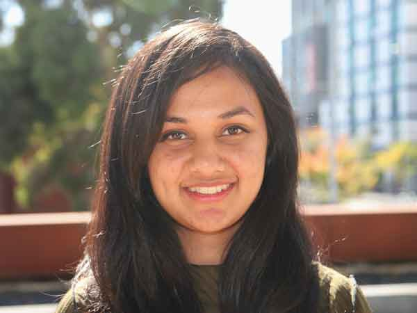 A headshot of Vandana, a Biotechnology student. Vandana is smiling at the camera, and pictured outside. She has brown hair and brown eyes.