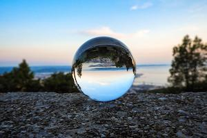 A glass globe resting on a hilltop. A coastal horizon is in the background - and reflected in the globe