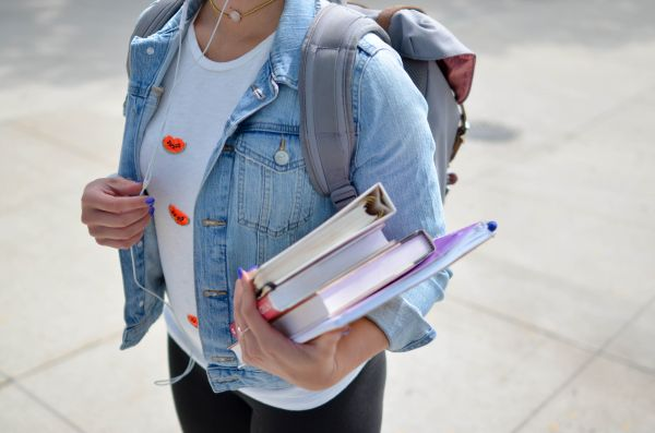 A person holding a stack of books. They are wearing a backpack.
