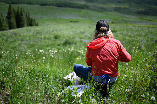 woman crouching in a field with a sample bag
