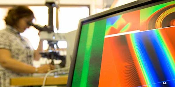 A screen showing spectrometer readouts - in the background is a student looking through an electron microscope