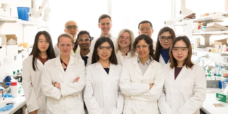 A group of international researchers, in white labcoats, posing together in a brightly-lit laboratory