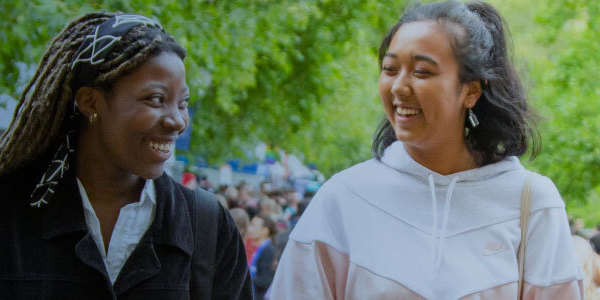 Two students smiling to each other, with a crowd of people and a lot of greenery visible behind them