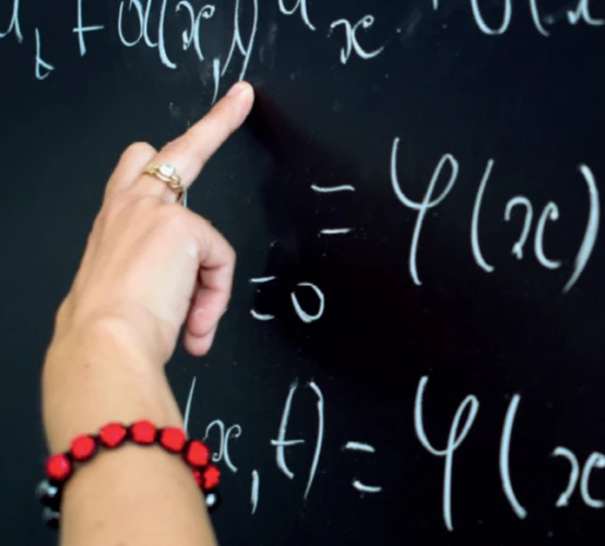A hand on a chalkboard pointing at mathematical equations