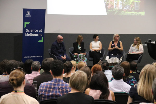 Four female and one male panellists sit on a stage, next to a 'Science at Melbourne' banner, in front of a full audience.