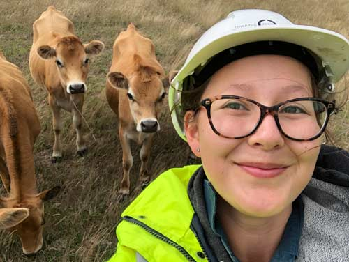 Henrietta Farr, in hard hat and hi-vis gear, with three calves behind her
