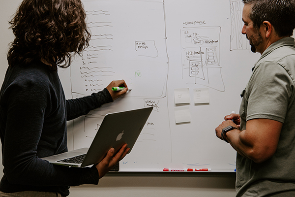 two people standing in front of a whiteboard