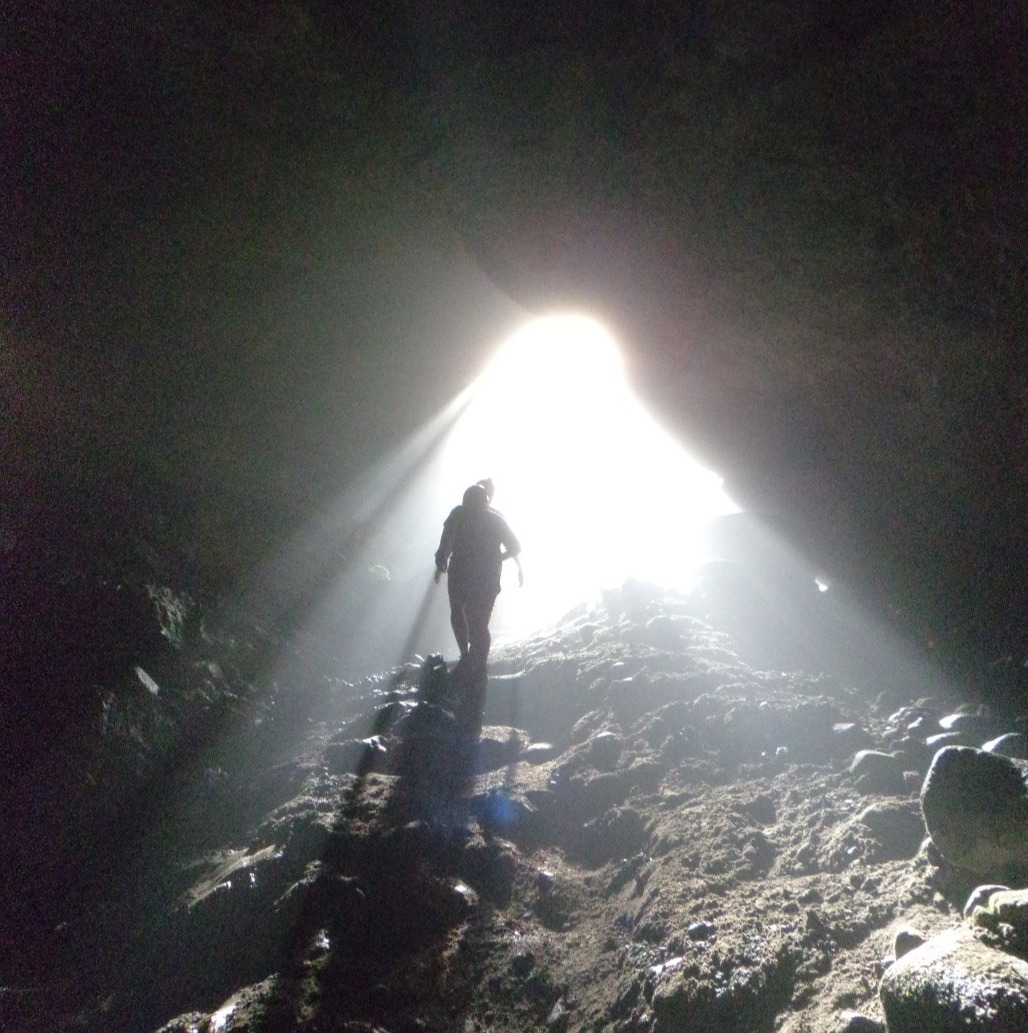 Light shining through a cave entrance from below the surface