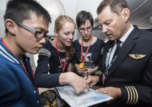A group of four people looking at a map of Antarctica on on aeroplane