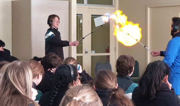 A student holds up a metal rod, a small explosion of fire and light comes off the end
